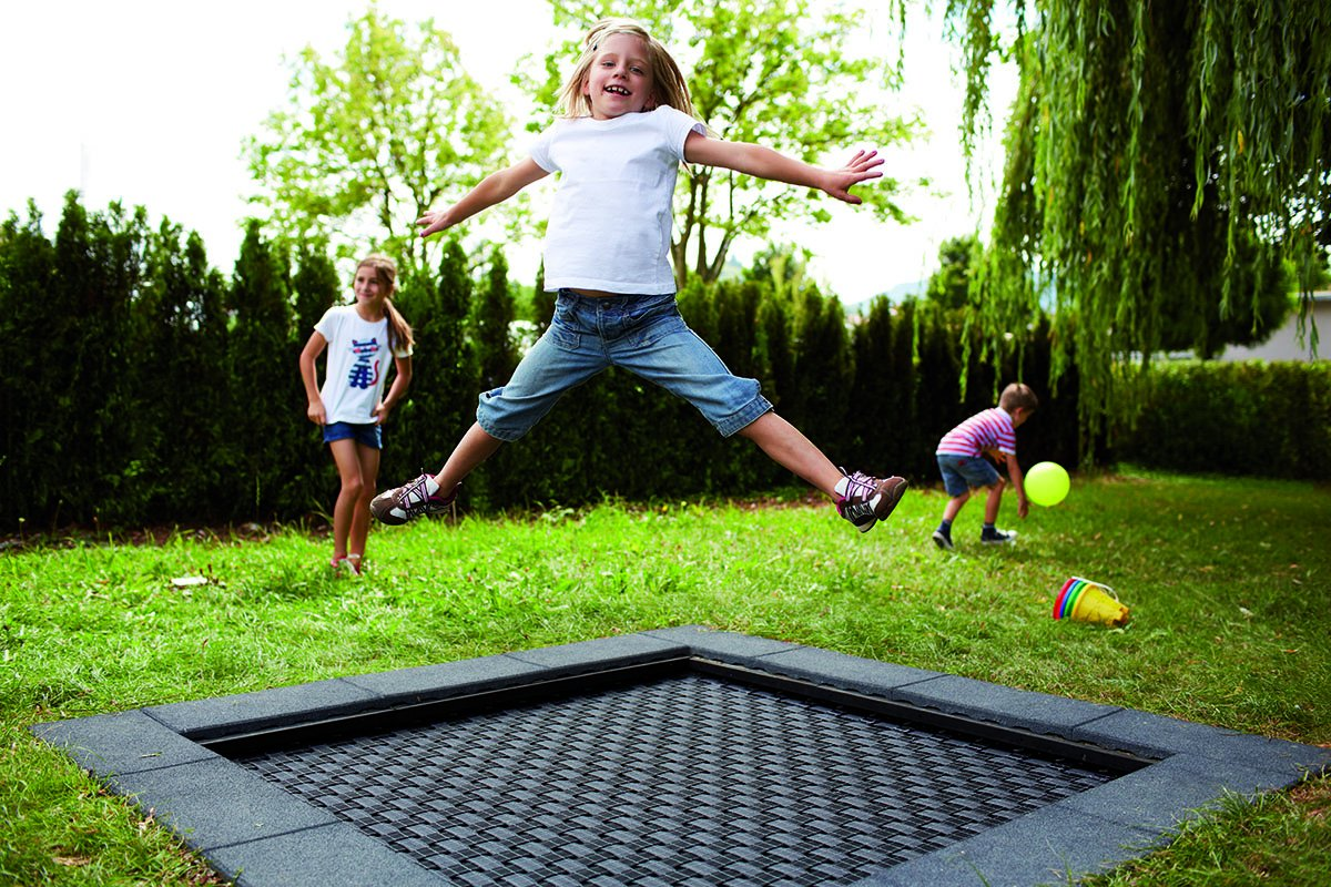 Square trampoline in the ground with jumping girl.